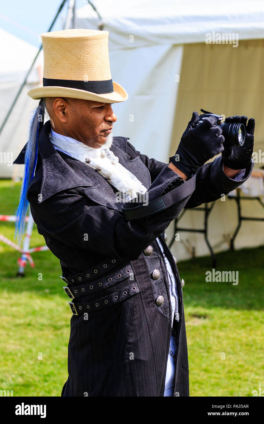 Afro-Caribbean man, 40s, dressed in steam-punk style Victorian clothing and straw hat, holding point and shoot camera while at event. - Stock Image