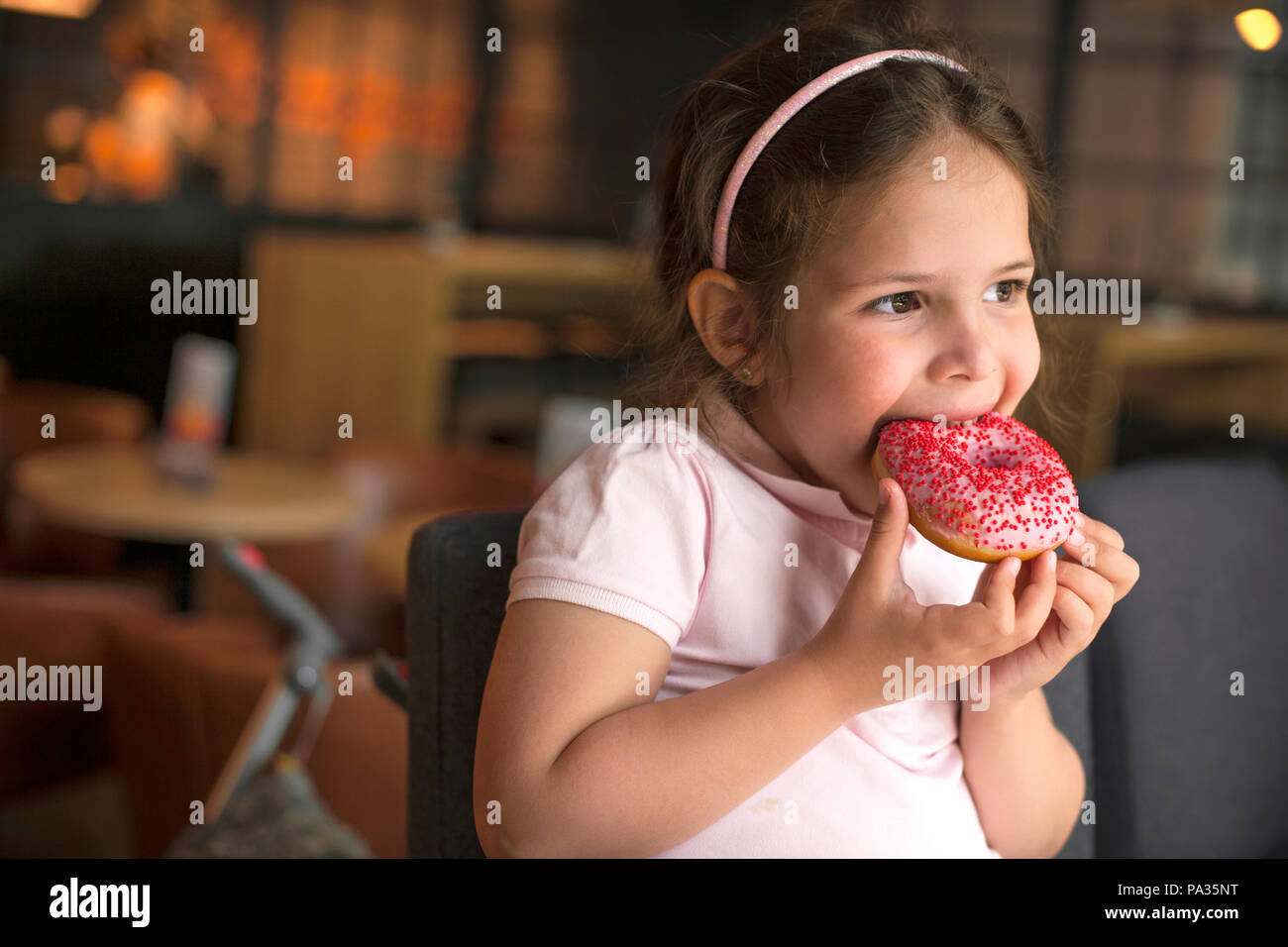 happy girl eating pastry at a cafe. Harmful sweet food. Trends in food. Copy space - Stock Image