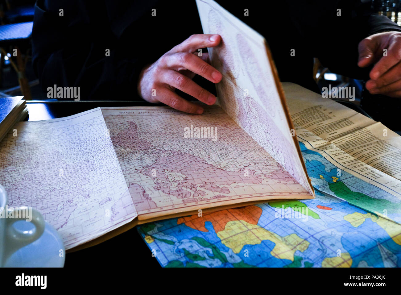 cropped view of adult man's hands opening up old printed map of world on kitchen table covered with other maps - Stock Image