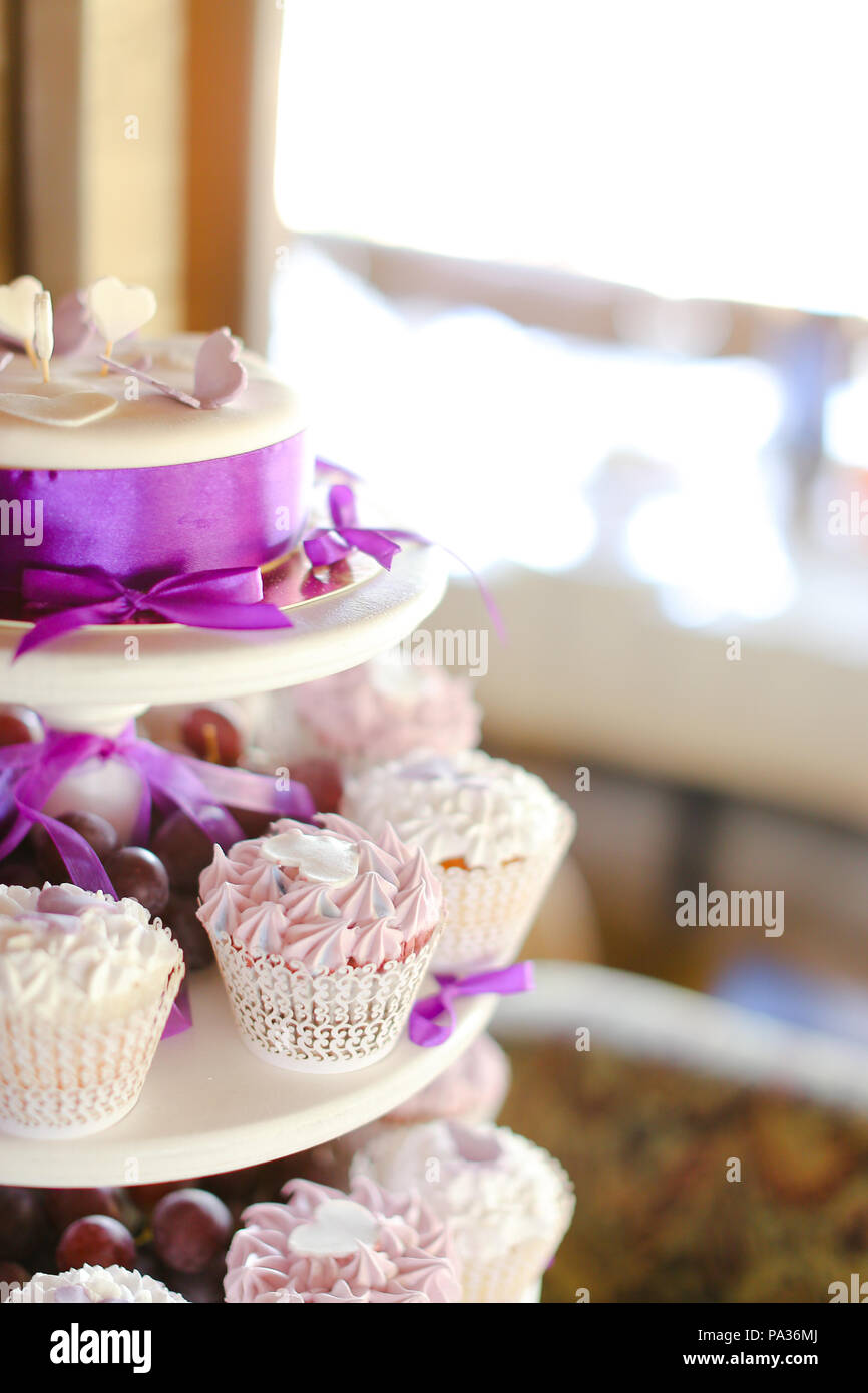 Violet decorations and sweet cakes for party. - Stock Image