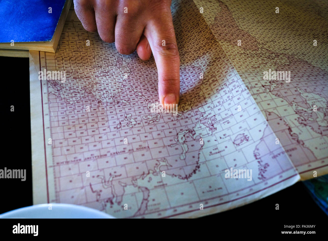 cropped view of adult man's finger pointing to a location on an old printed map of world on kitchen table - Stock Image