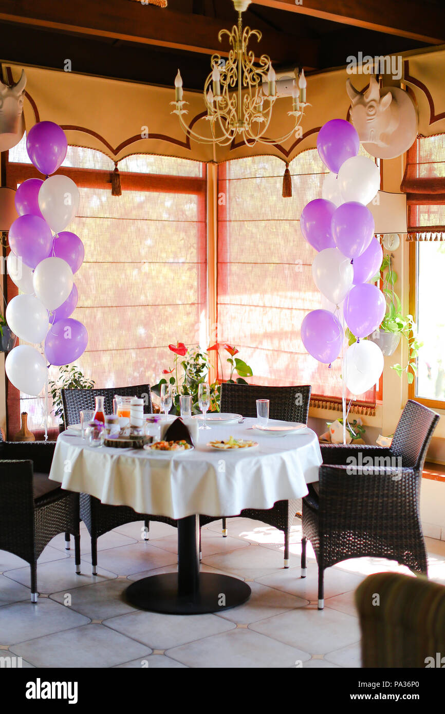 Food on table at cafe and white violet ballons. - Stock Image