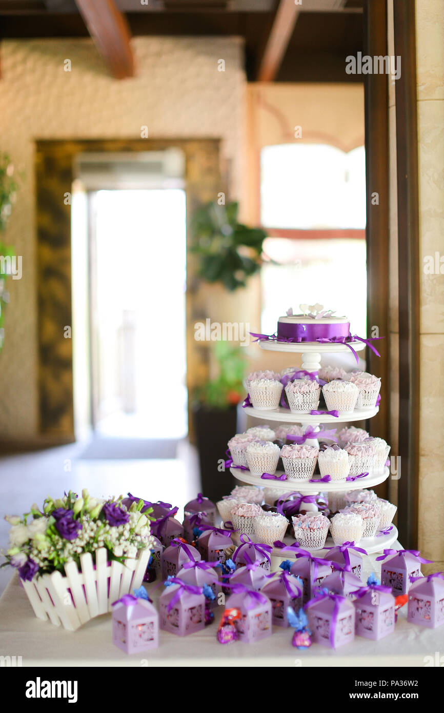 Violet decorations and sweet delicious cakes for party. - Stock Image