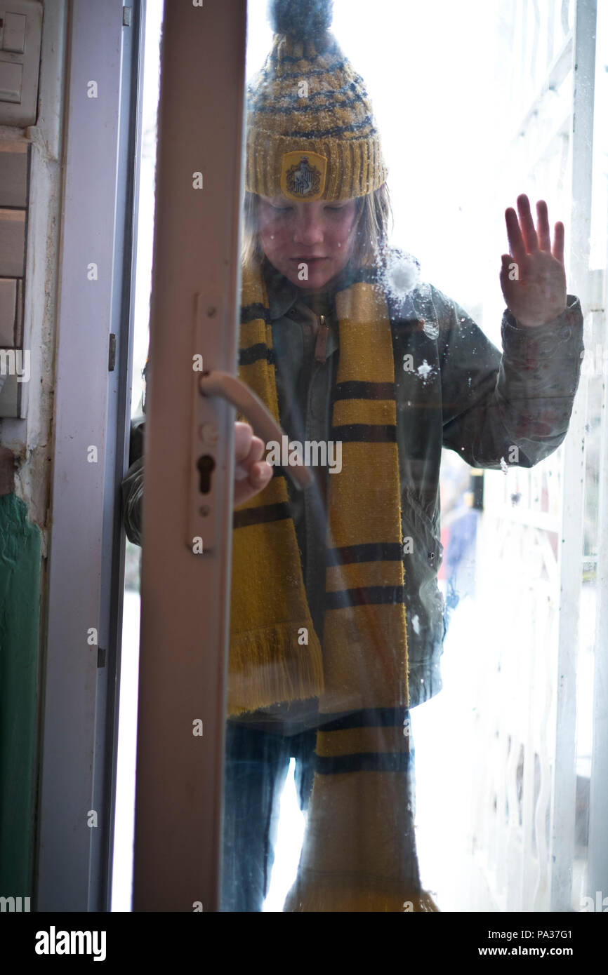 emotive low angle shot of ten year old boy dressed in winter clothes coming into his home after snowball fight - Stock Image