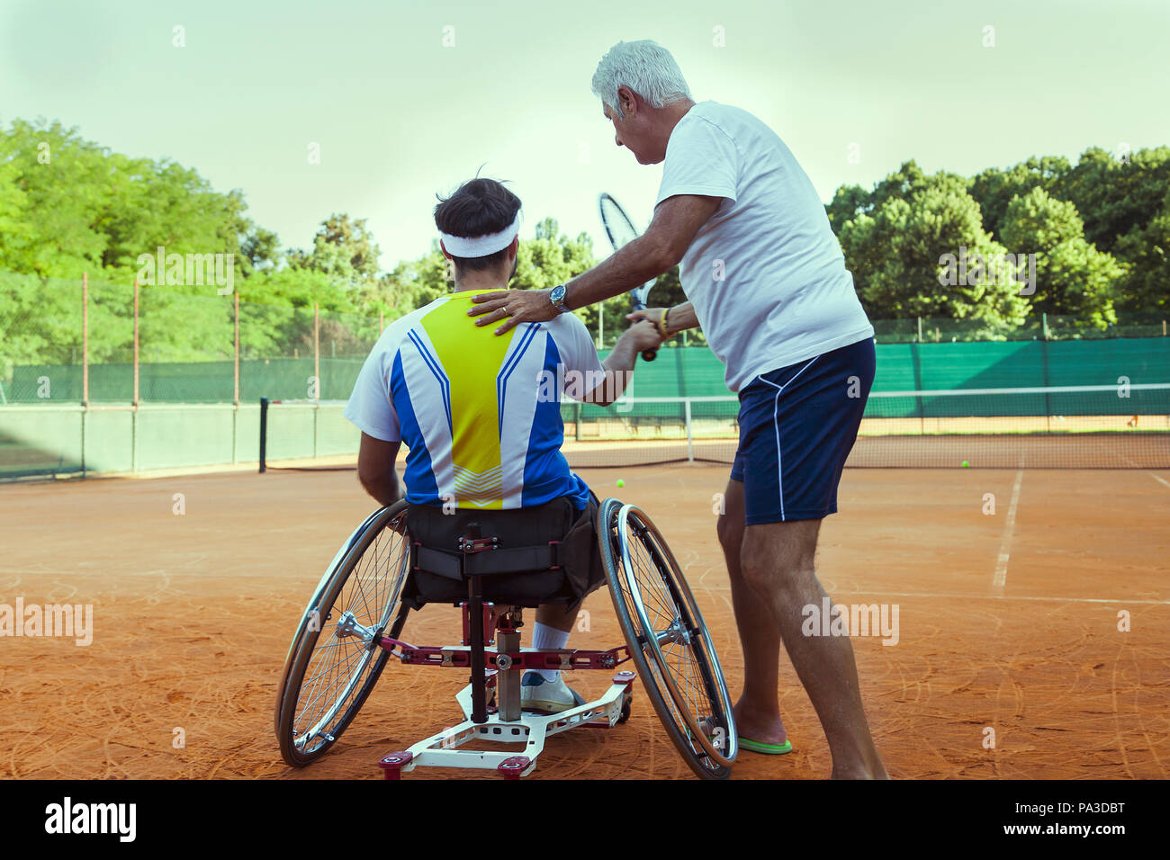 tennis coach teaching a disabled player the correct movement of the backhand outdoor - Stock Image