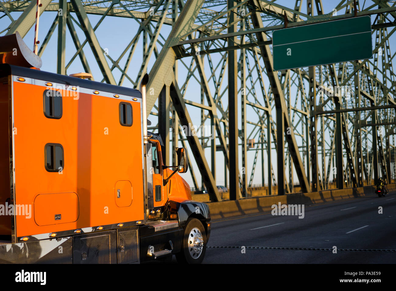 Orange big rig long haul semi truck with extra long cabin for truck driver rest driving alone interstate highway transporting commercial cargo moving  - Stock Image