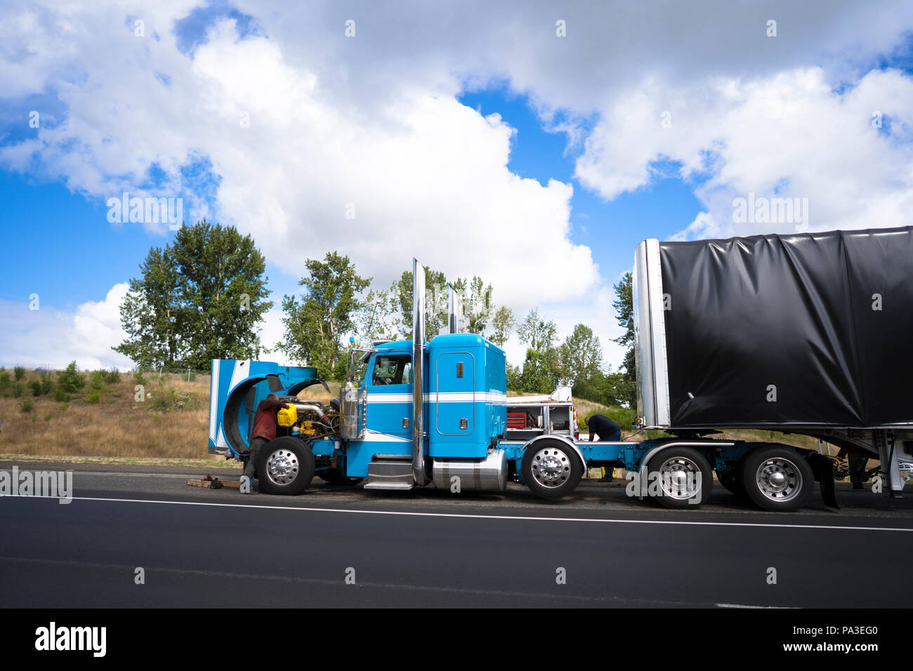 Truck drivers repairing big rig blue bonnet semi truck with open hood breakage occurred during the delivery of the goods and carry covered loaded semi - Stock Image