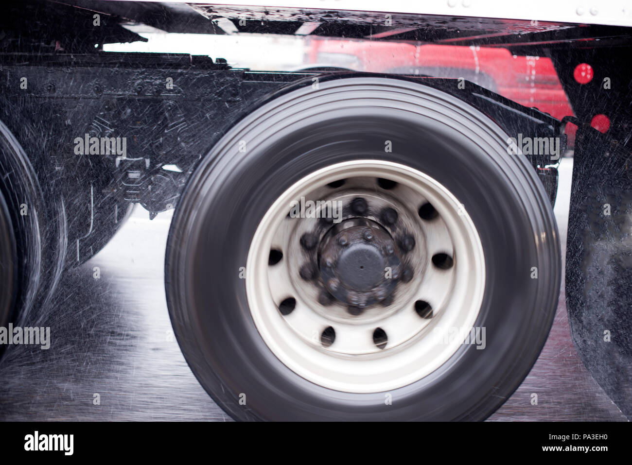 Rotary wheels of long haul moving on the highway big rig semi truck with semi trailer raises rain dust from the wet road surface with light reflection - Stock Image
