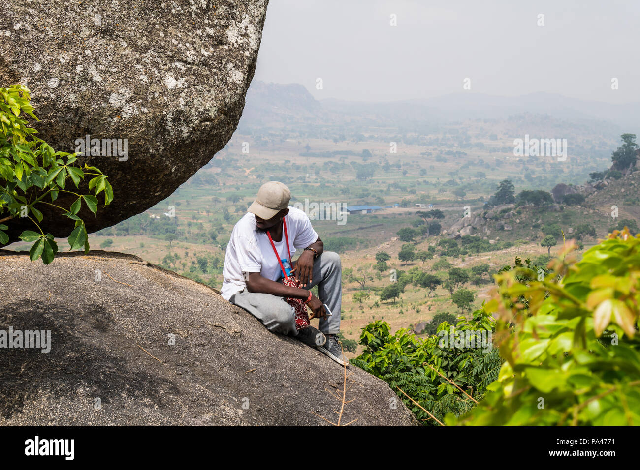 An unknown young man reminiscing on the top of a hill overlooking a landscape. - Stock Image