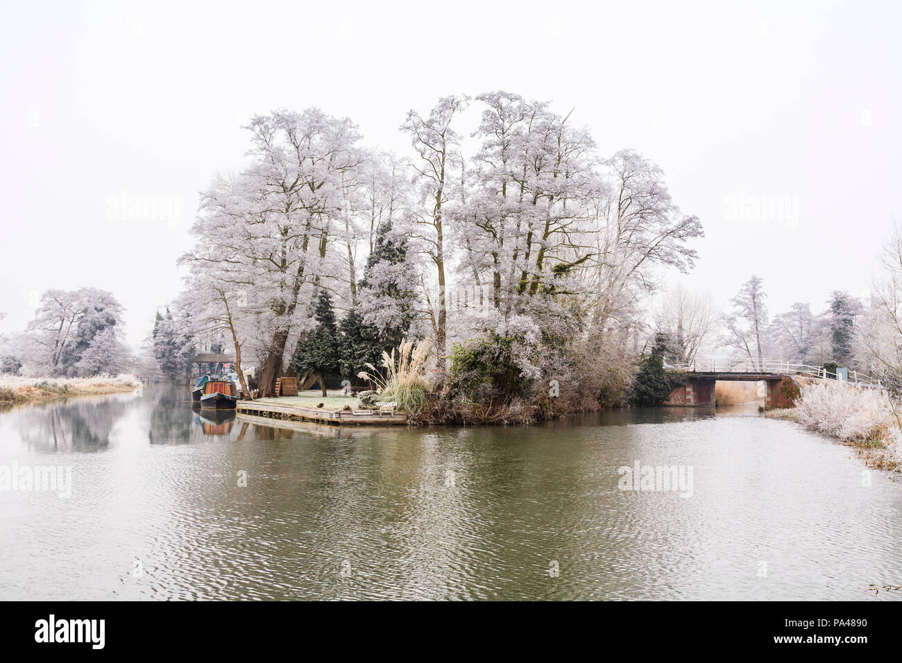 Rural Surrey landscape, southeast England, River Wey with moored narrowboat and road bridge near Pyrford in low temperature freezing winter weather - Stock Image