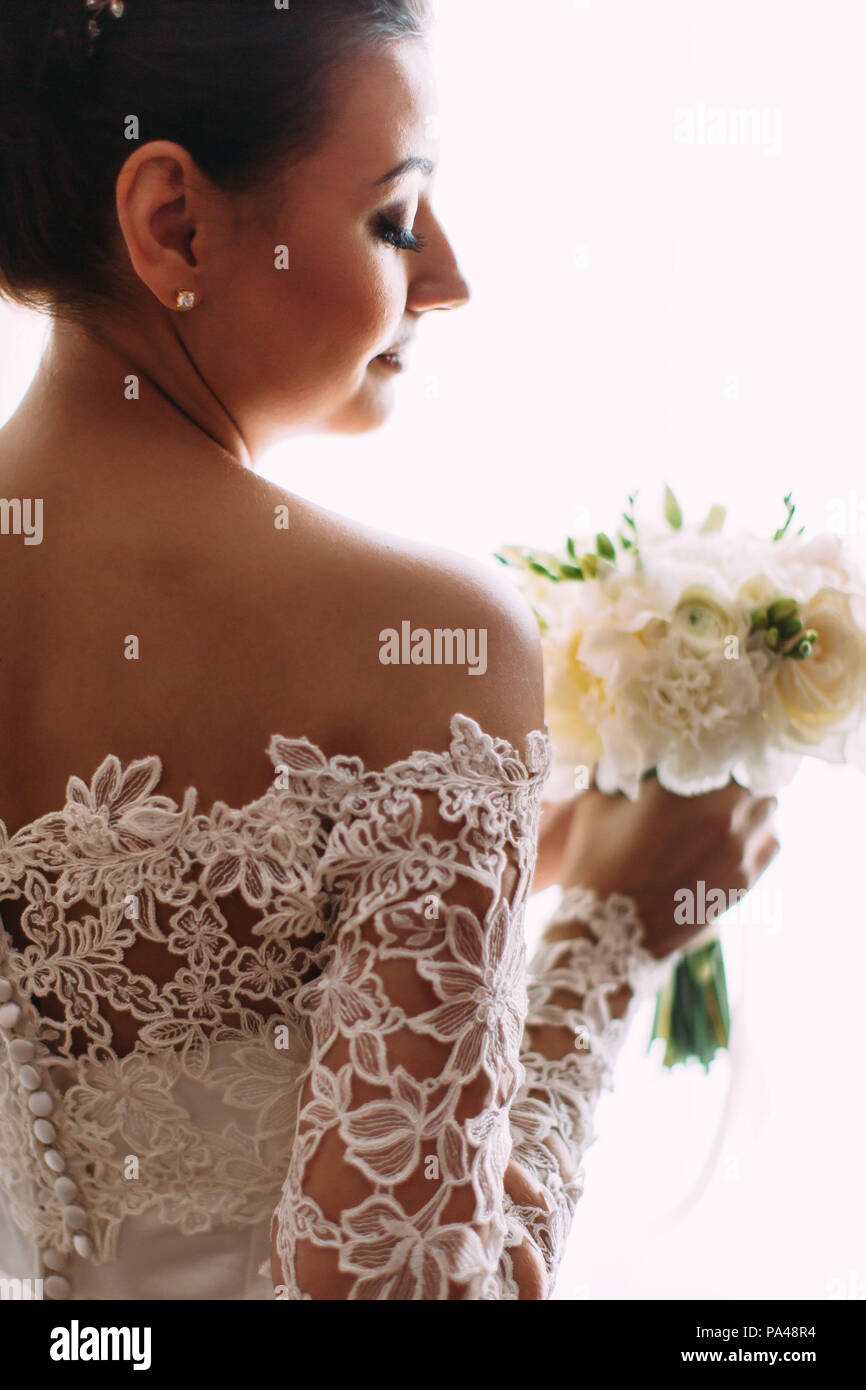 The Back View Of The Bride In Lace Dress Holding The Wedding