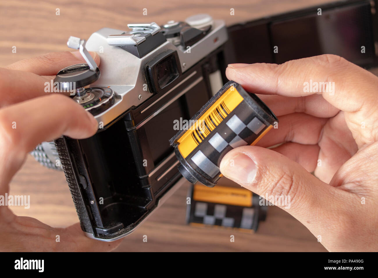 Placing a 35mm film to an analog camera manually - Stock Image