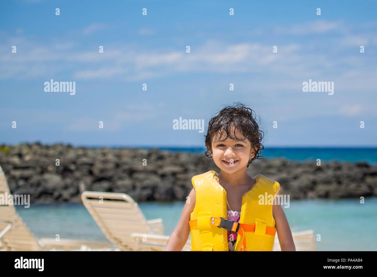 Little Girl In a Life Vest on an Ocean Beach - Stock Image