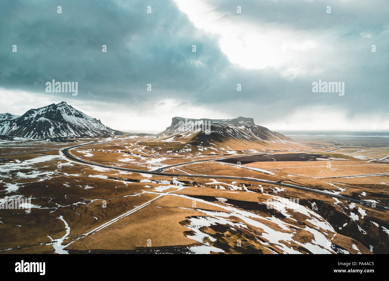Iceland aerial view Landscape with snow and clouds, street and yellow and green grass - Stock Image