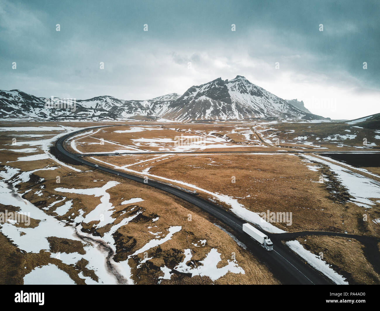 Iceland , February 2018: A truck is passing along a street with aerial view of Landscape with snow and clouds street and yellow and green grass. - Stock Image