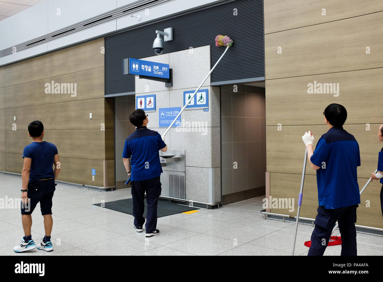 Workers — one with an extra-long  mop — cleaning Incheon International Airport in Seoul, South Korea. - Stock Image