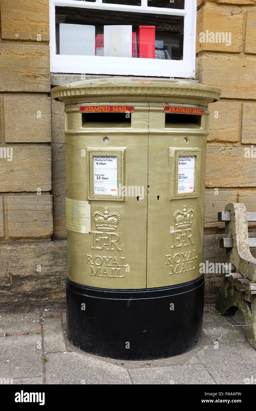 A gold-painted post box, one of many throughout the U.K. celebrating gold medal winners at the 2012 Summer Olympics and 2012 Summer Paralympics. - Stock Image