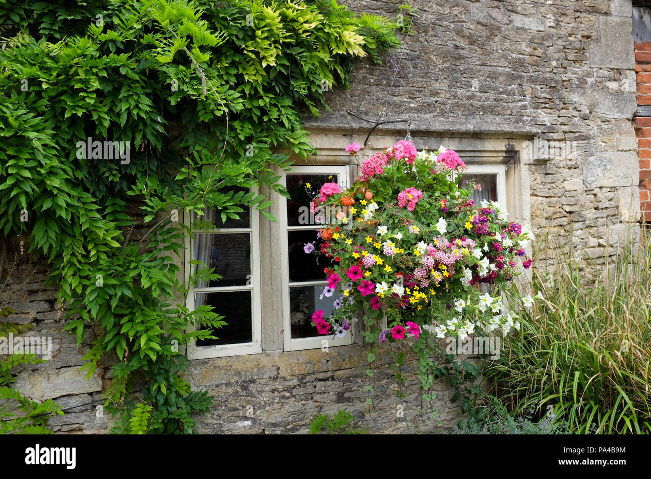 Hanging baskets in the village of Lacock in Wiltshire, England. - Stock Image