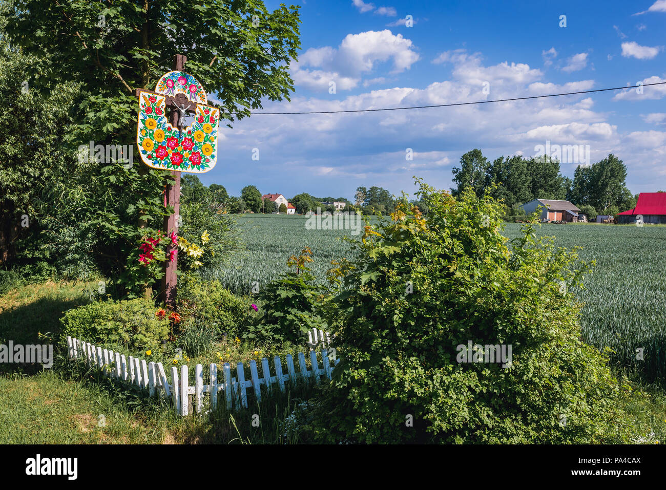 Wayside cross in Zalipie village in Poland, known for its local tradition of floral paintings made famous by folk artist Felicja Curylowa - Stock Image
