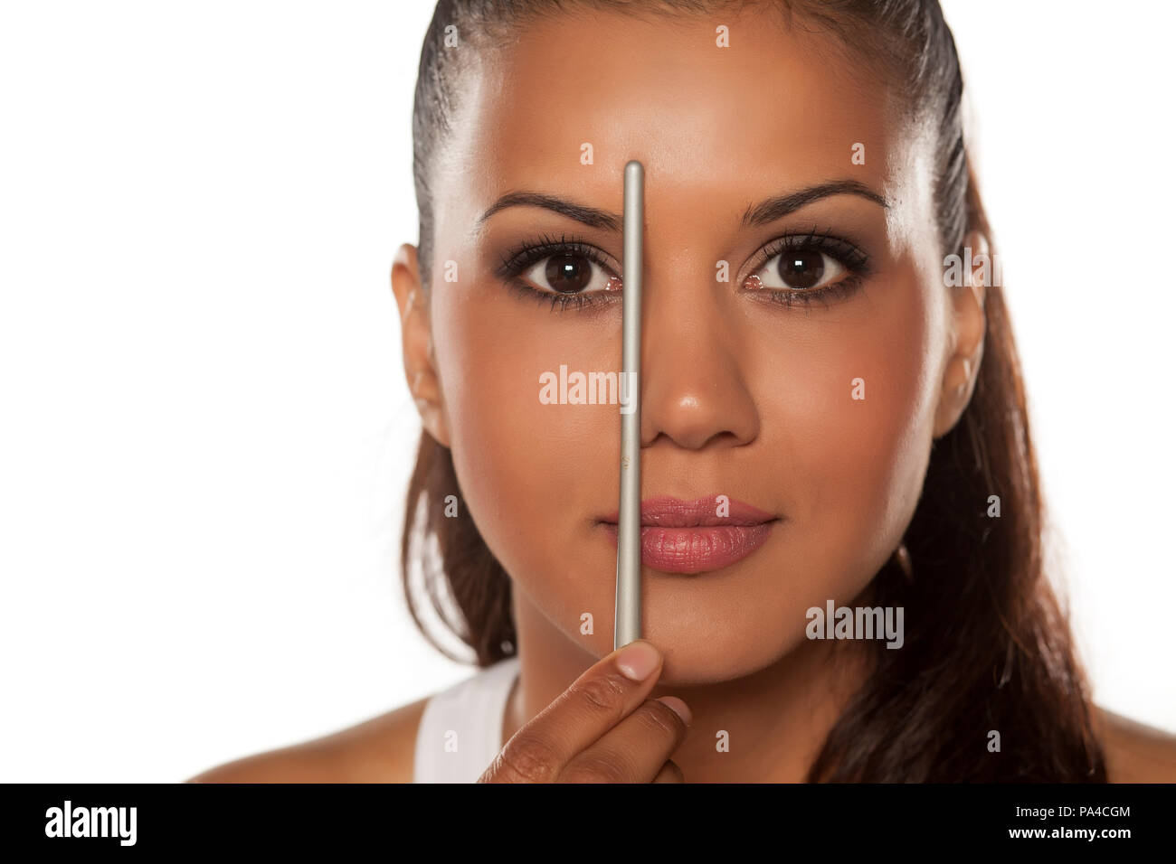 young beautiful latina shows the correct length and shape of the eyebrows - Stock Image