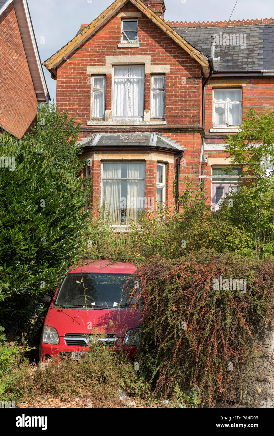 poorly maintained house with overgrown garden - Stock Image