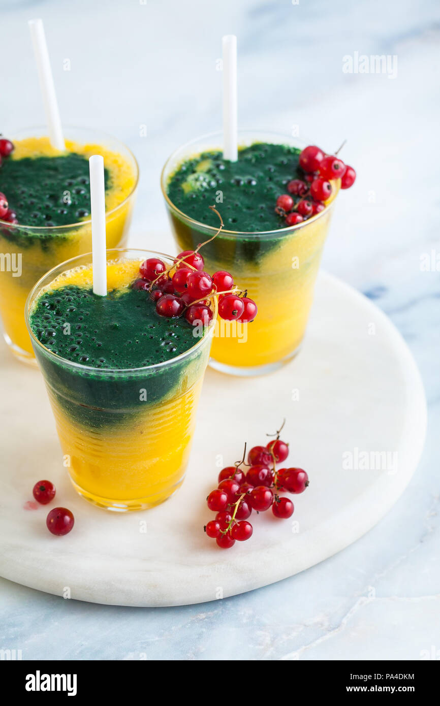 two colored fresh smoothies in glasses with fresh berries
