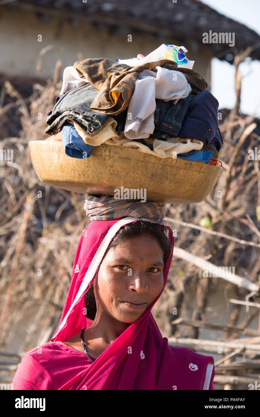 Indian woman carrying her clothes basket on her head in Kanha village near the Kanha National Park, in India Stock Photo