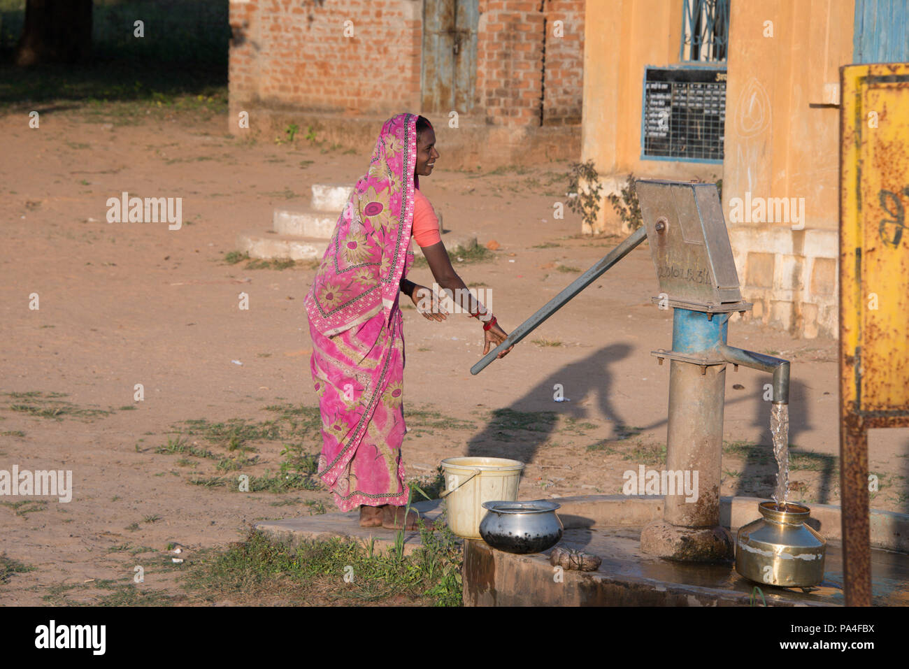Indian woman pumps water from a well in the local village in Kanha near the Kanha National Park, in India - Stock Image