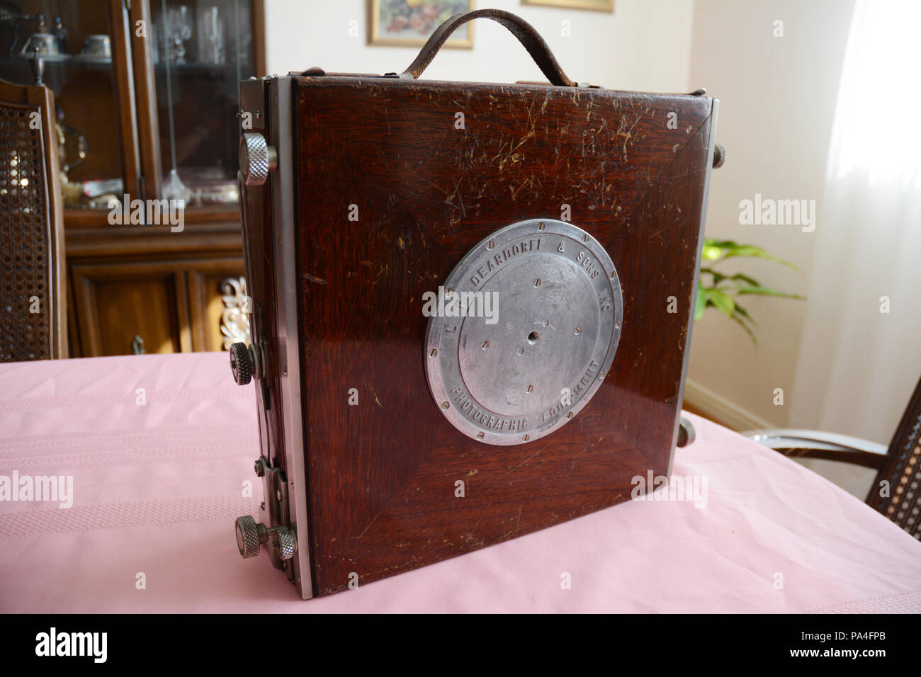 The front of a foldable large format Deardorff antique 8x10 analog field camera, in its collapsible form with carrying handle, built in the 1950s. - Stock Image