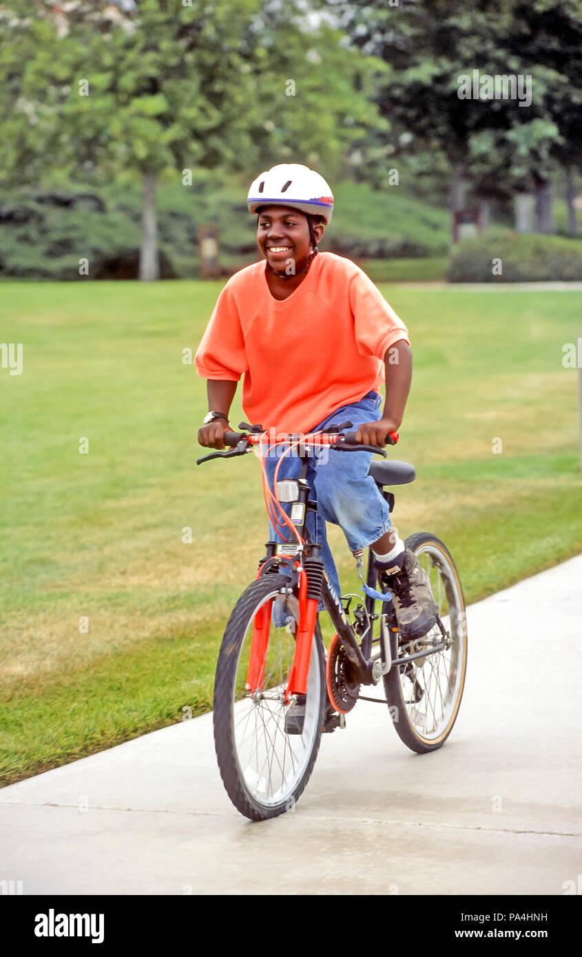 Boy 11-13 years old riding bike on path © Myrleen Pearson