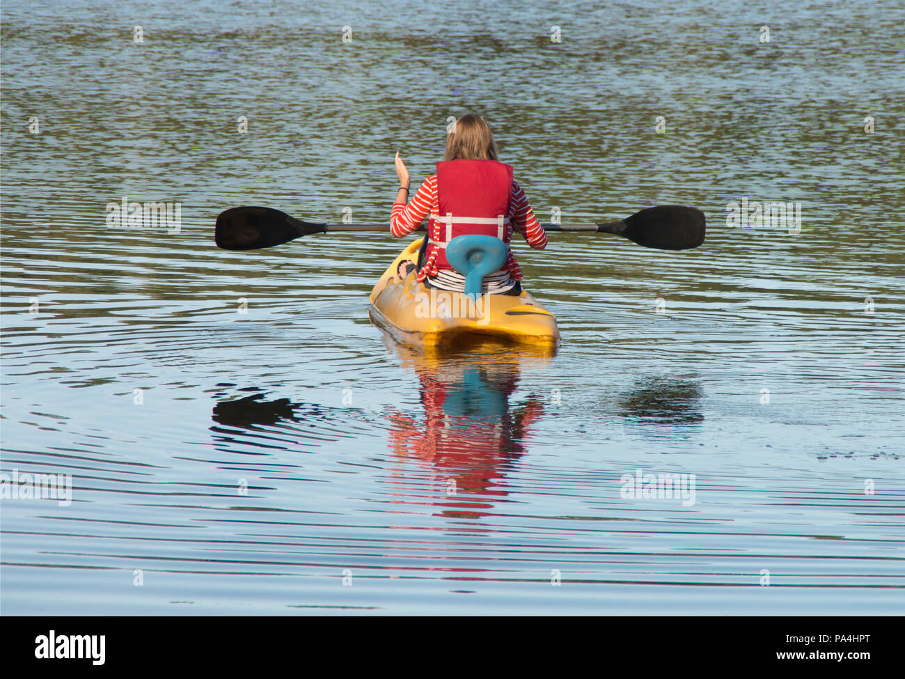 A woman heads out on her kayak to explore a small lake in a campground in ,Charleston ,South Carolina - Stock Image