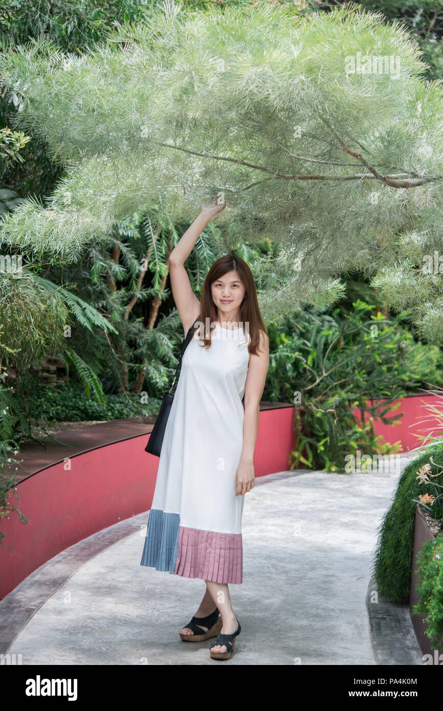 Portrait of sweet young Asian women wearing white dress and posing in the Flower Dome of Garden By The Bay, Singapore-  A man made Green house. - Stock Image