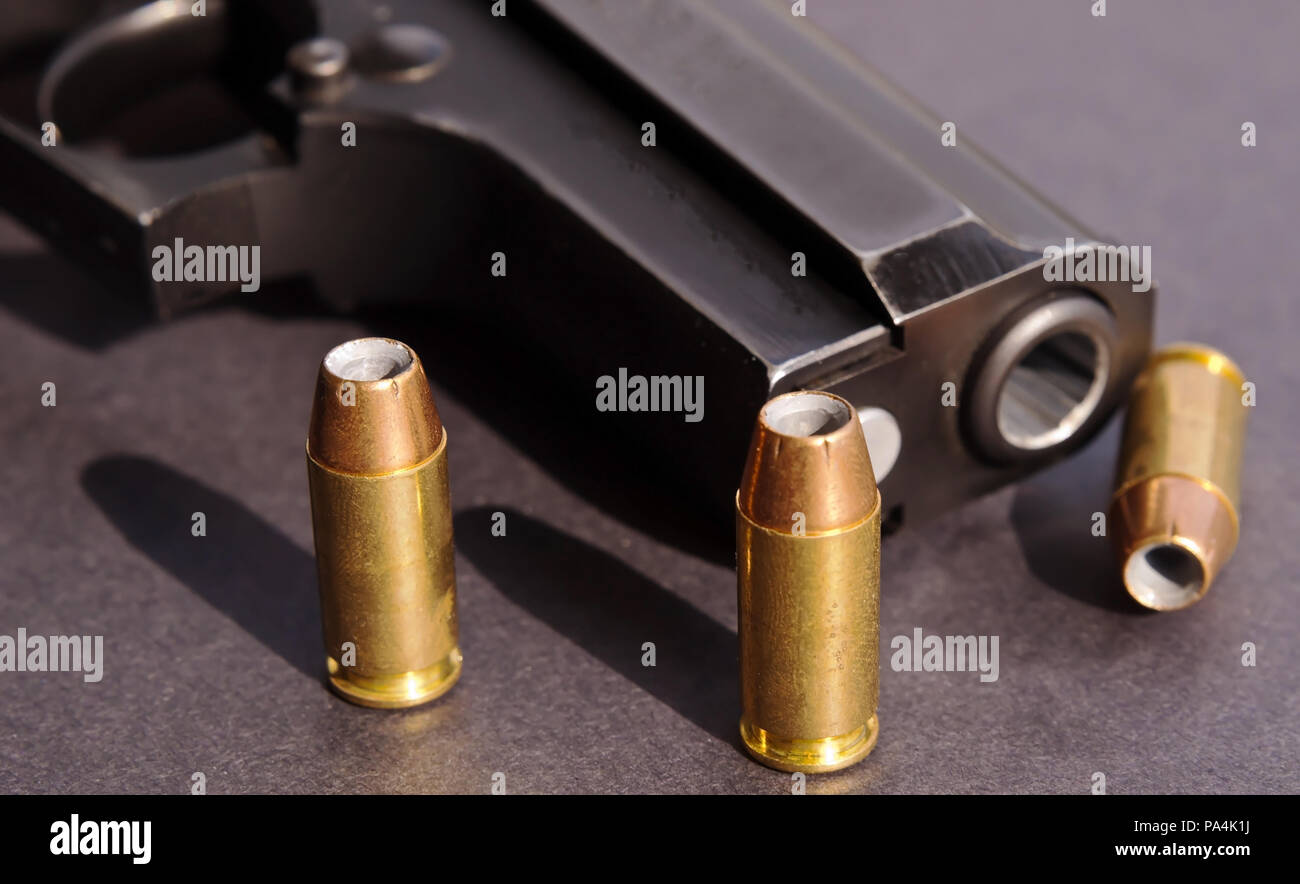 Three hollow point bullets casting shadows on a black background next to a black pistol - Stock Image