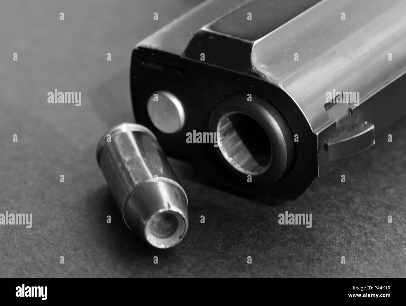 A single 40 caliber hollow point bullet standing next to the muzzle of a black pistol on a black background shown in black and white - Stock Image