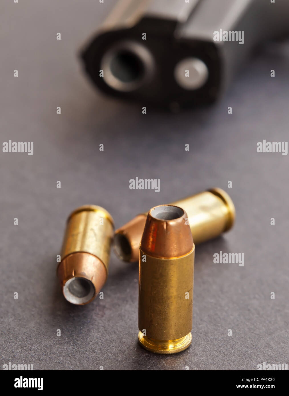 Three 40 caliber hollow point bullets on a black background with a black pistol laying behind them showing only it's muzzle - Stock Image