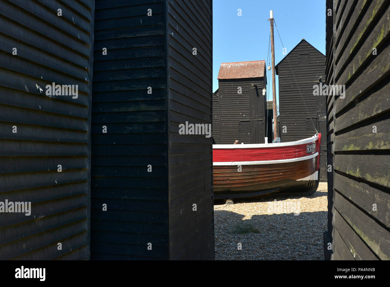 Fishing huts, net sheds or net shops, and historic boats in Hastings Old Town, East Sussex UK - Stock Image