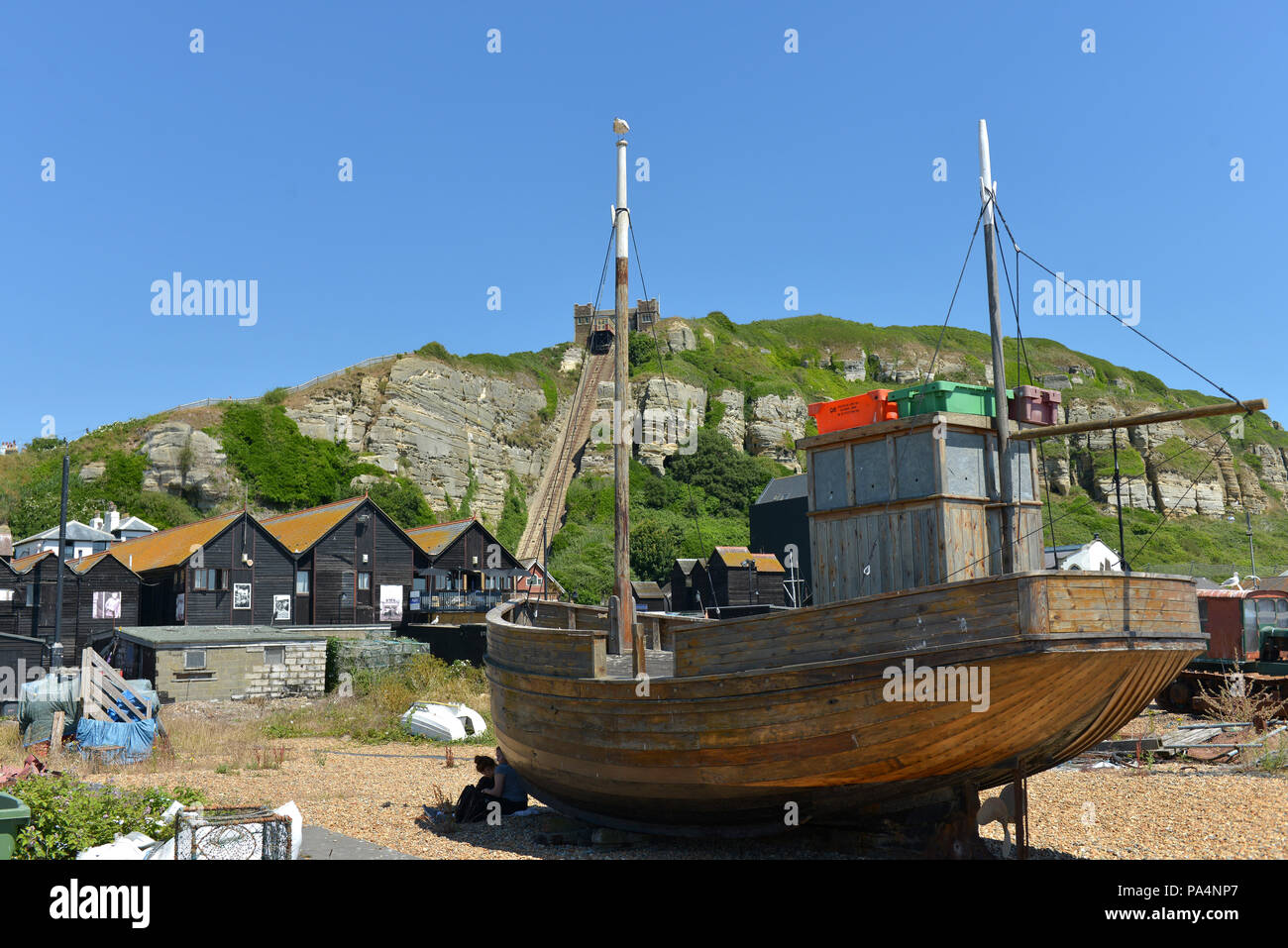 Fishing boats and net huts on the Stade, Hastings Old Town beach, with East Hill Cliff railway. - Stock Image