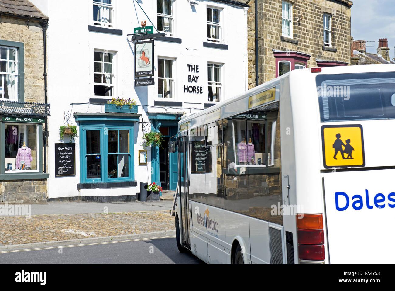 Bus passing the Bay Horse pub, Masham, North Yorkshire, England UK - Stock Image