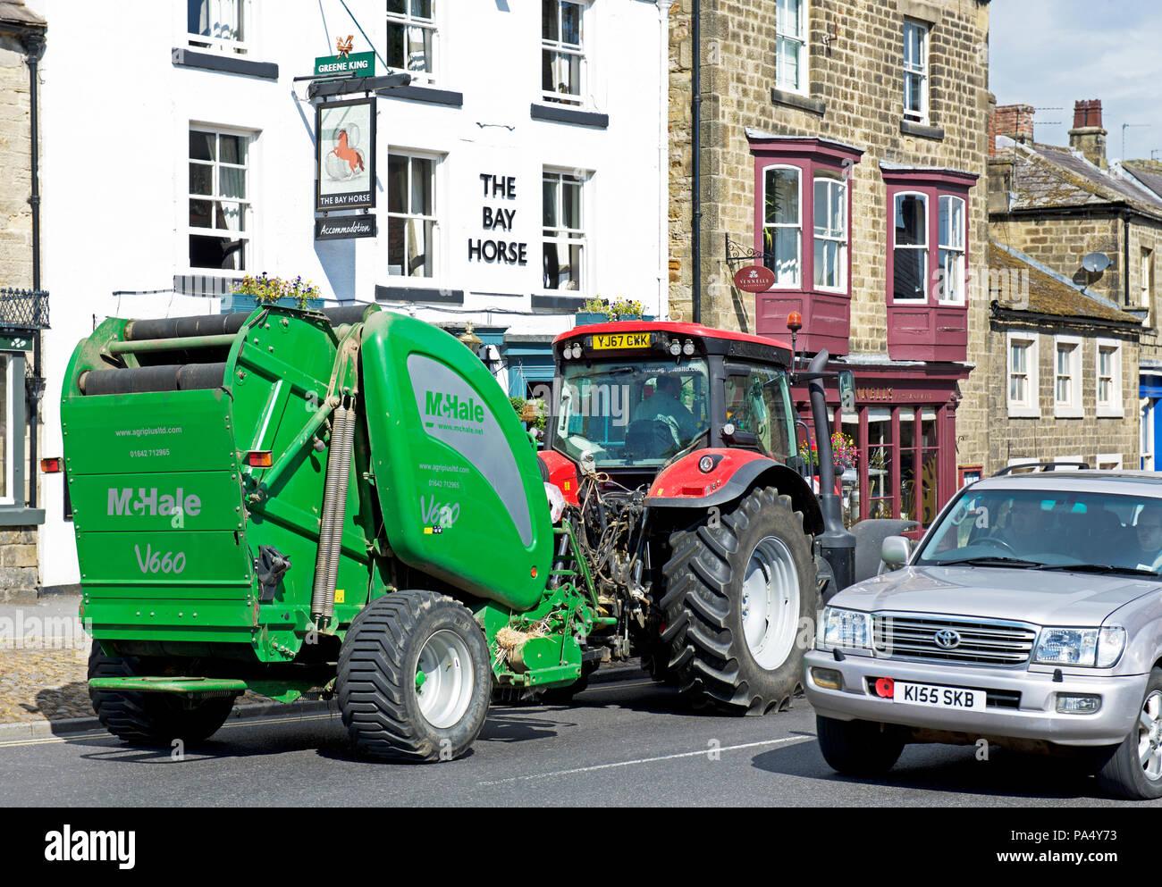 Tractor passing the Bay Horse pub, Masham, North Yorkshire, England UK - Stock Image