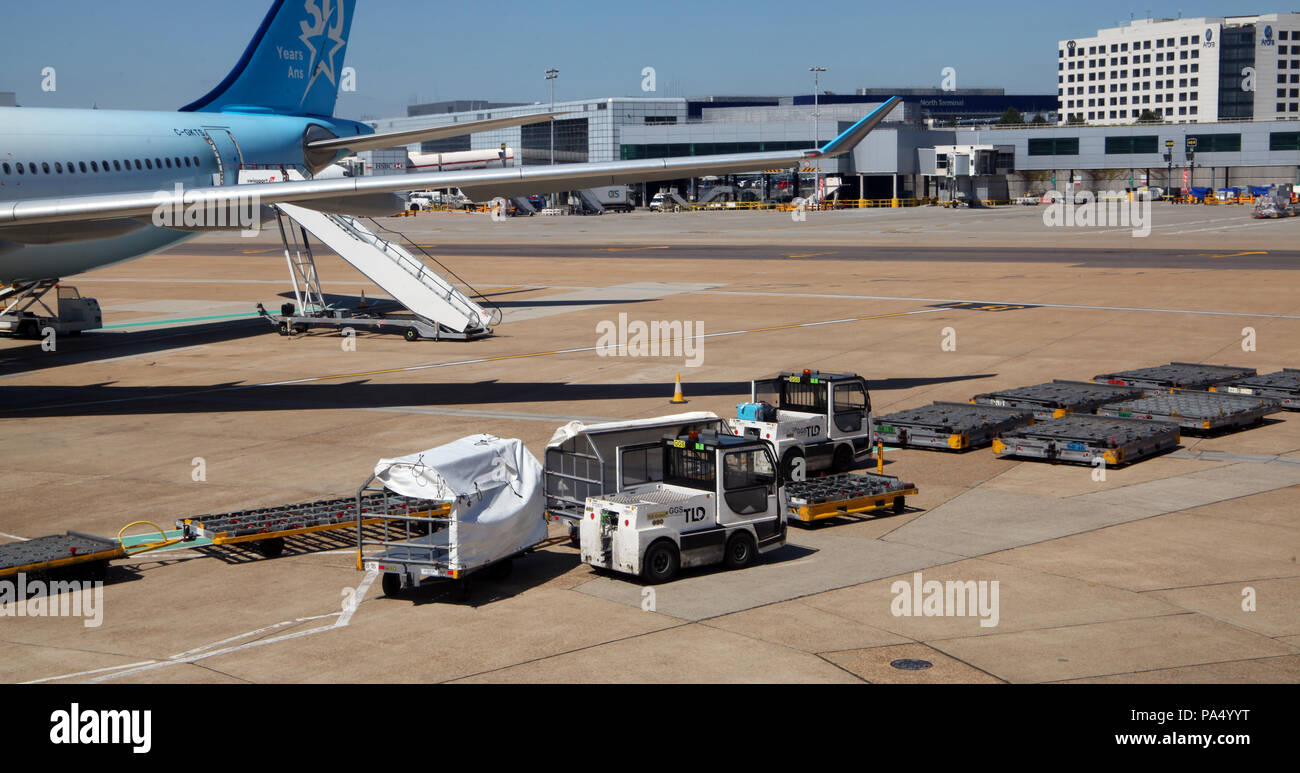 equipment to handle passenger baggage on the apron at London Gatwick Airport - Stock Image