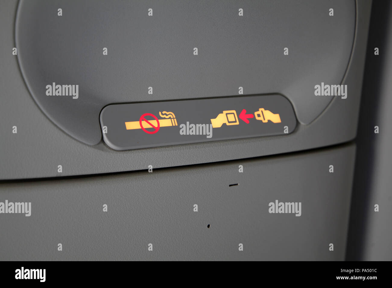 no smoking & fasten seat belts sign on a passenger aircraft - Stock Image
