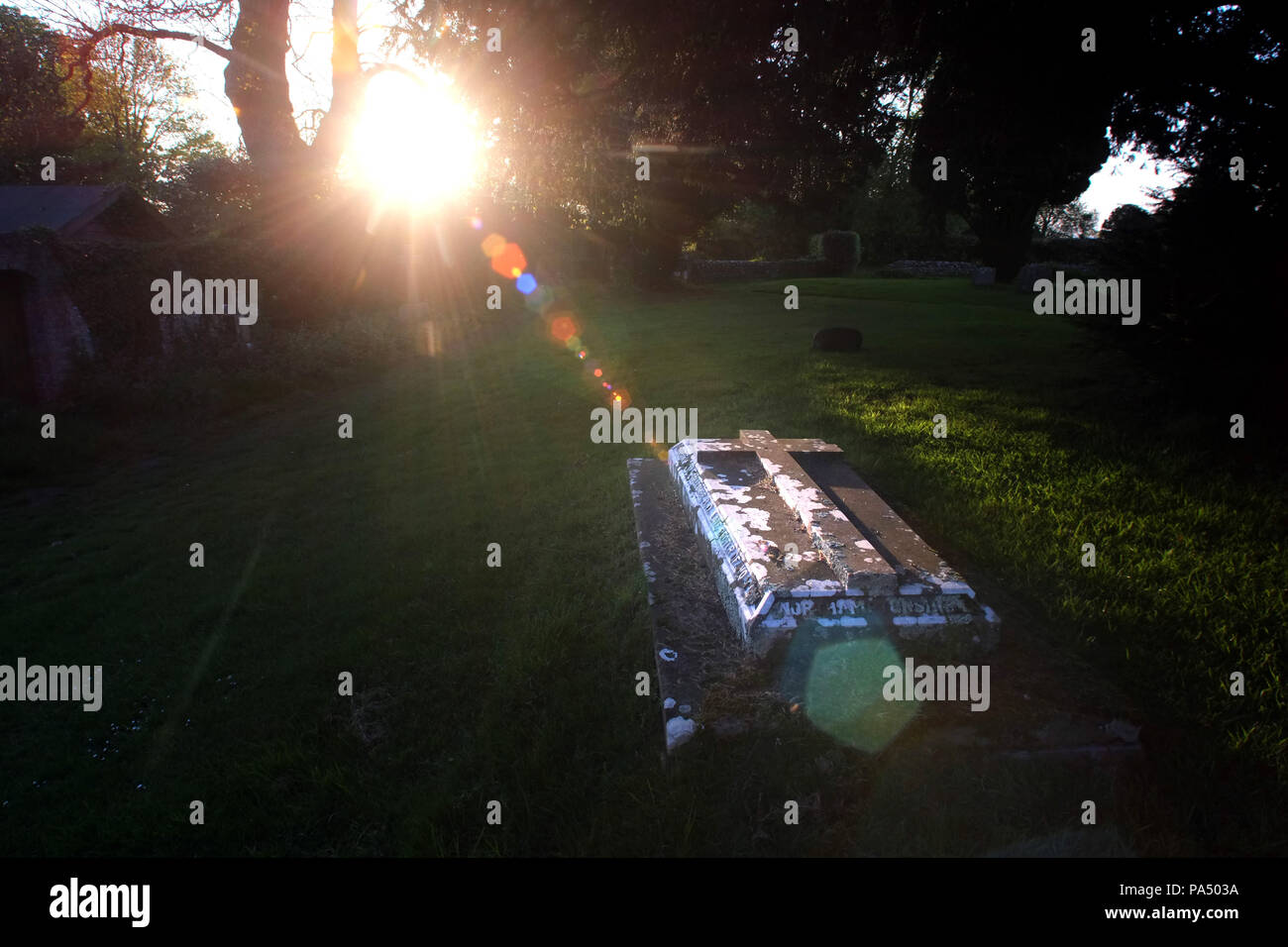 Sunbeam illuminating a grave in a parish churchyard. - Stock Image