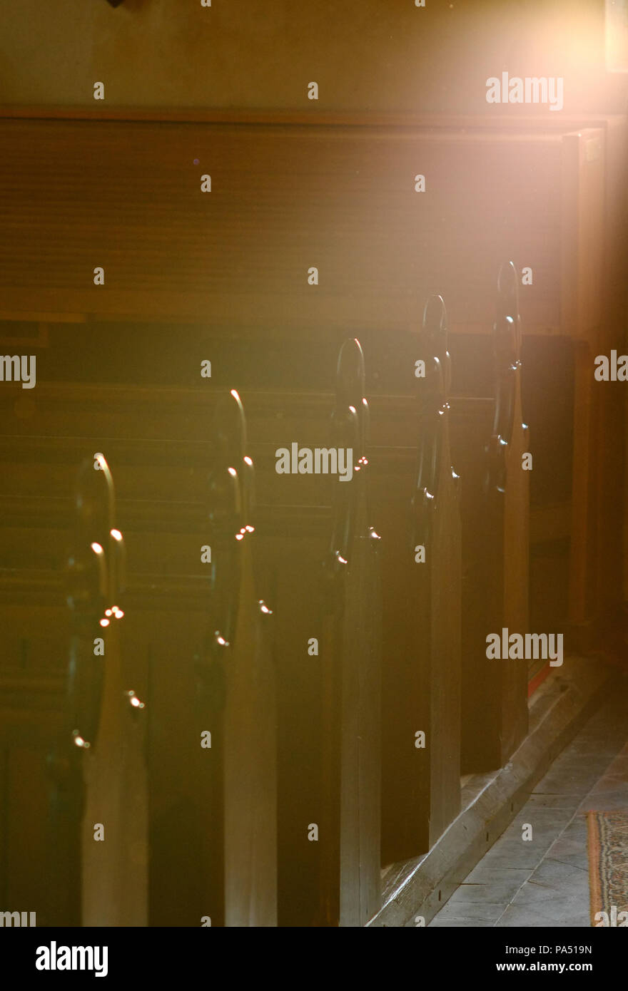 Row of church pews with fluer de lys carvng with atmospheric lighting. Stock Photo