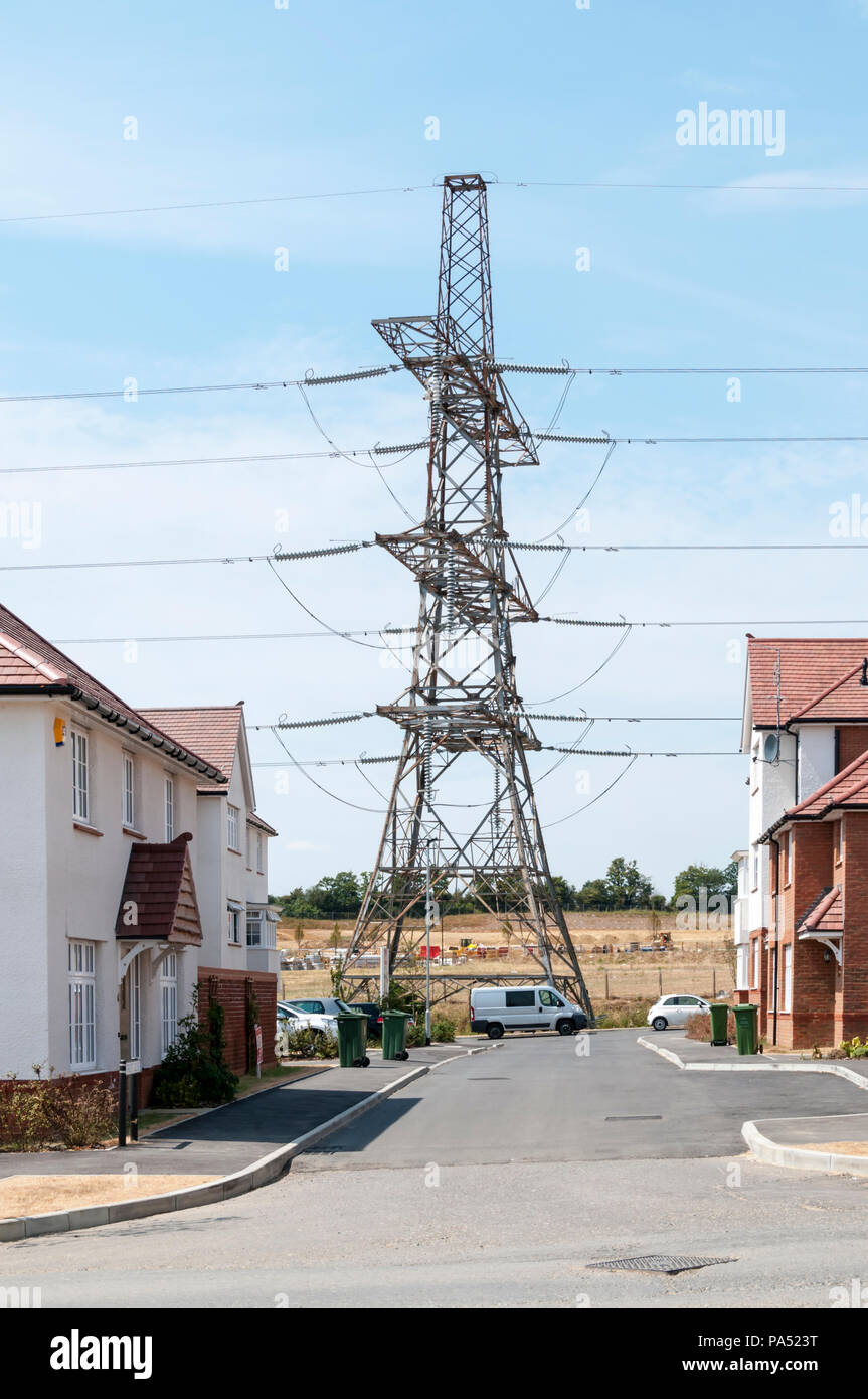A transmission tower or electricity pylon carries an overhead line across a housing area at the Ebbsfleet Garden City development. - Stock Image