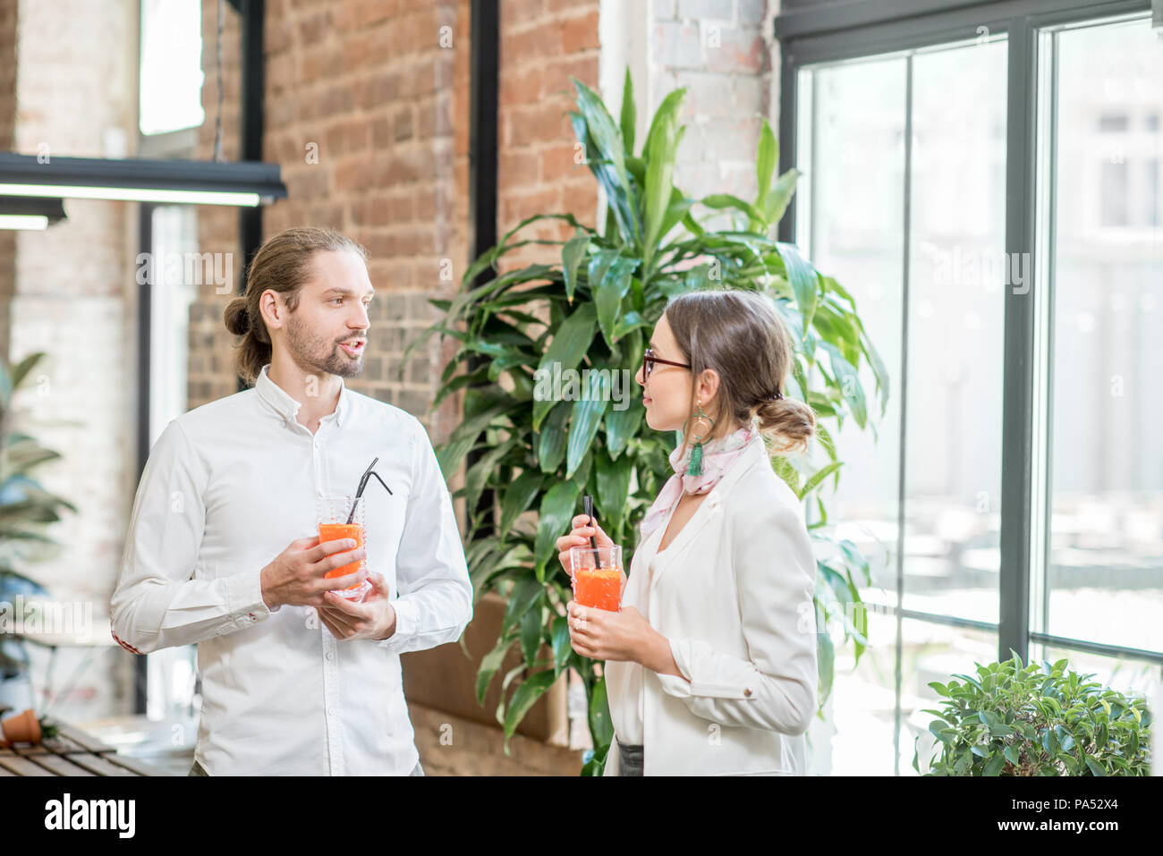 Young couple dressed in white standing together with drinks during the conversation in the beautiful loft interior Stock Photo