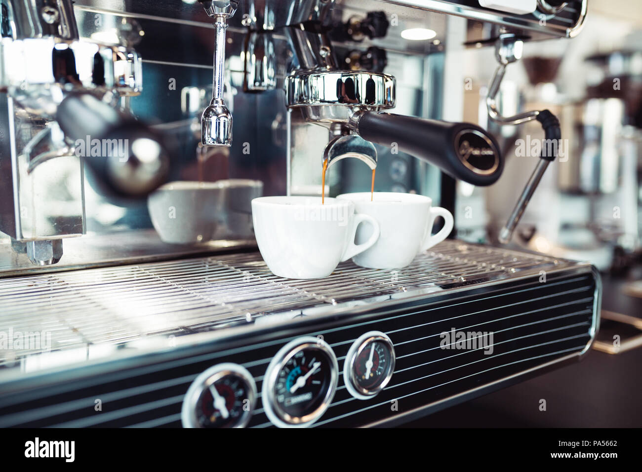 Espresso pouring from coffee machine into coffee cup. - Stock Image