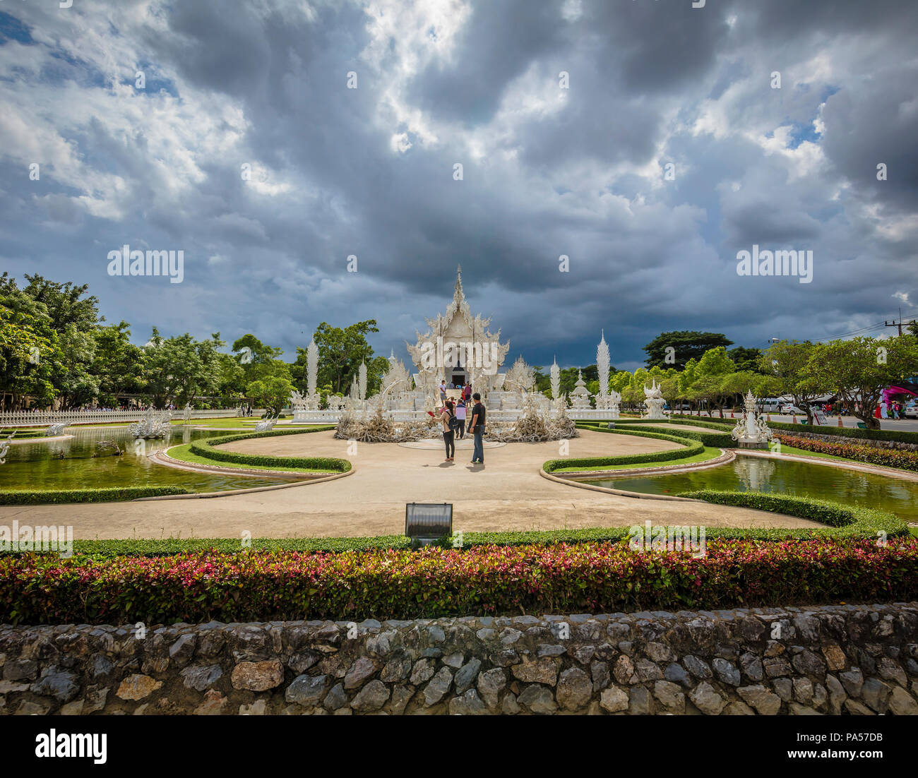 Chiang Rai (Thailand) - 10 June 2017: People are visiting the Wat Rong Khun, better known as the White Temple, a contemporary and unconventional Buddh Stock Photo