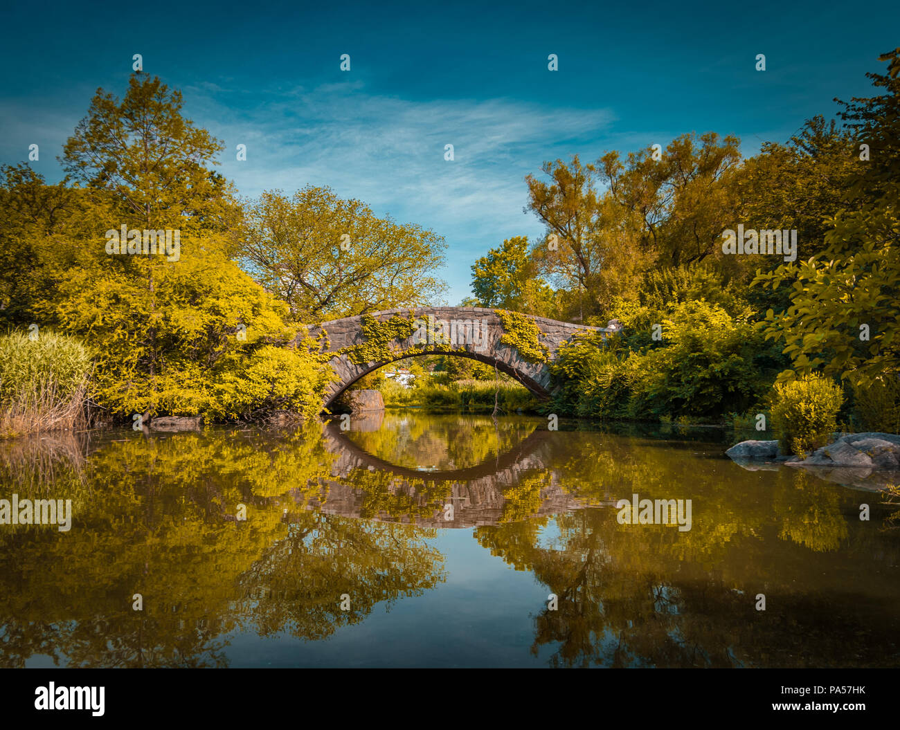 Gapstow bridge in Central Park in autumn reflecting in the water - Stock Image