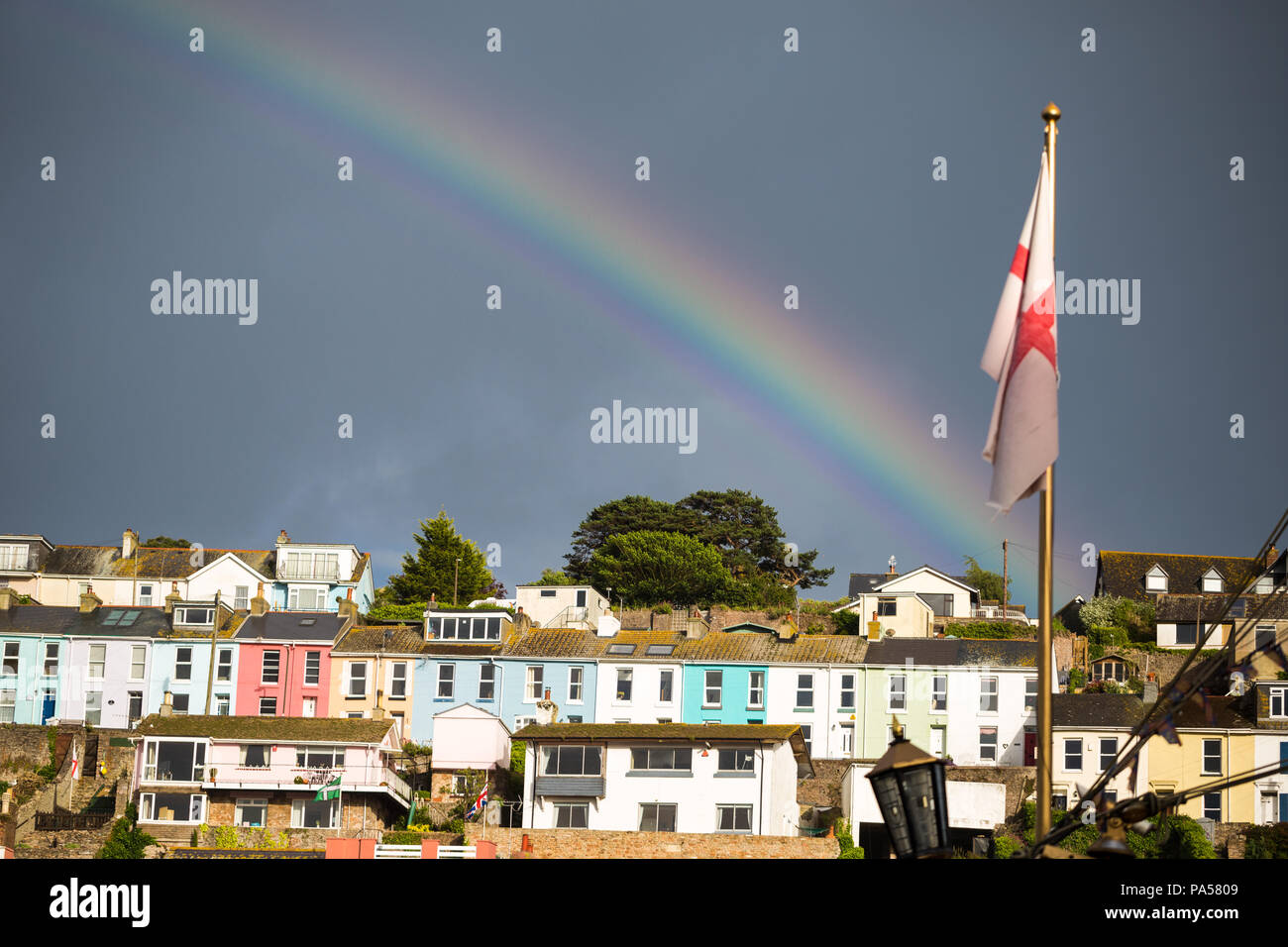 Colourful seaside homes with dark sky and rainbow, with St. Georges Cross English flag, Brixham, Devon - Stock Image