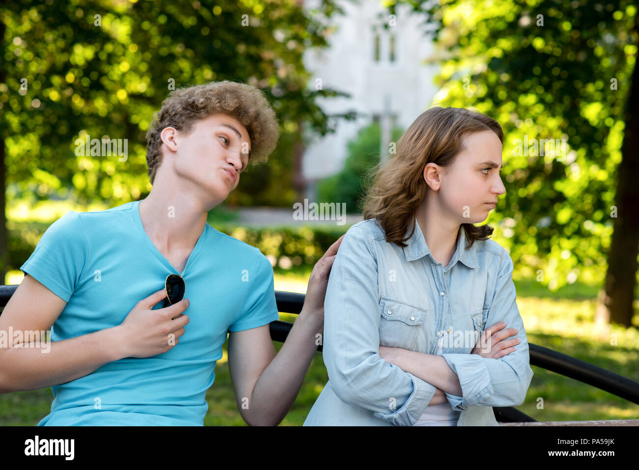 A guy with a girl on a park bench. In summer in the city. The guy asks girl for forgiveness. The girl is unhappy upset there is no reluctance to talk. - Stock Image